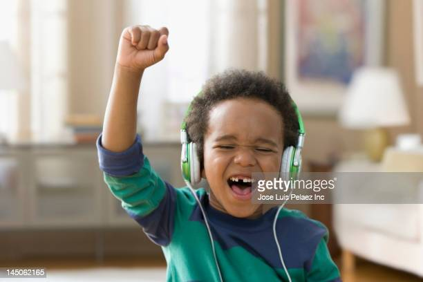 Black boy listening to music on headphones