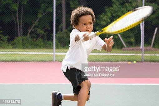 Black boy playing tennis : Stock Photo