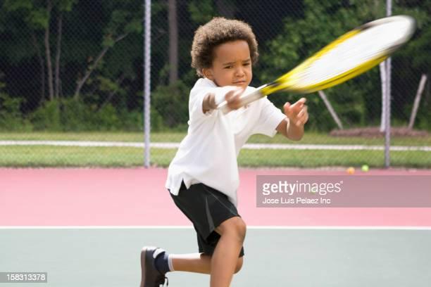 Black boy playing tennis