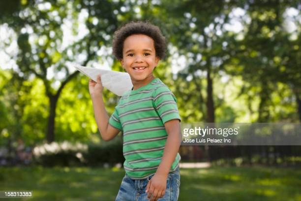 Black boy playing with paper airplane