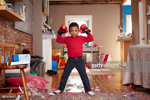 Black boy posing with boxing gloves in messy living room
