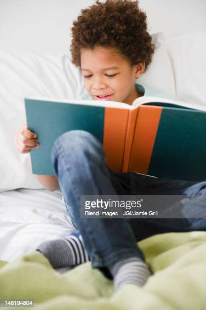 Black boy reading book in bed