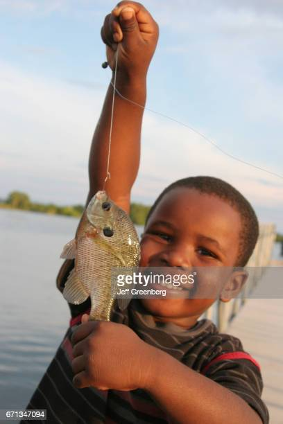 A black boy showing off the fish he caught from Chattahoochee River