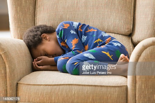 Black boy sleeping in armchair : Foto stock