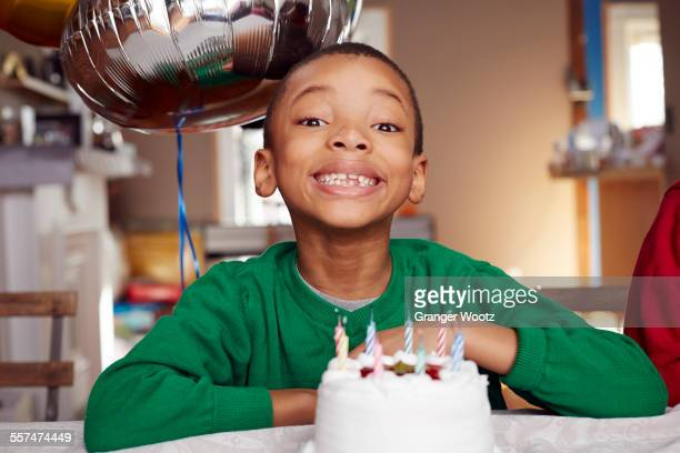 Black boy smiling with balloon and cake at party