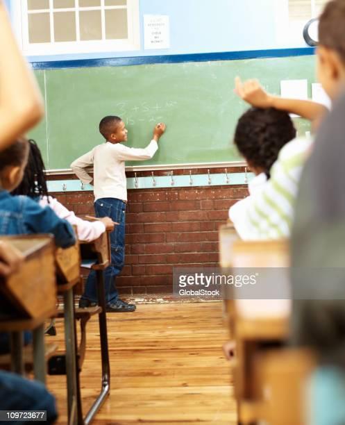 Black boy solving math on blackboard in classroom