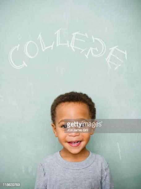 Black boy standing underneath the word college on blackboard