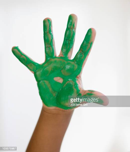 Black boy with green paint on hand