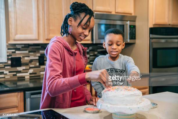 Black brother and sister decorating cake in kitchen