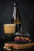 Black burger with dark bBlack homemade burger with stews and red cabbage served on small wooden chopping board with glass and bottle of dark beerer