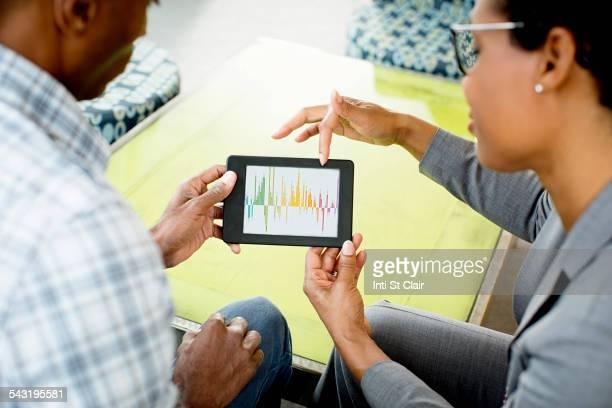 Black business people using digital tablet in office lobby