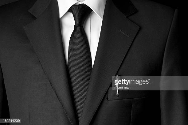 Black business suit and tie with a white shirt and a pen