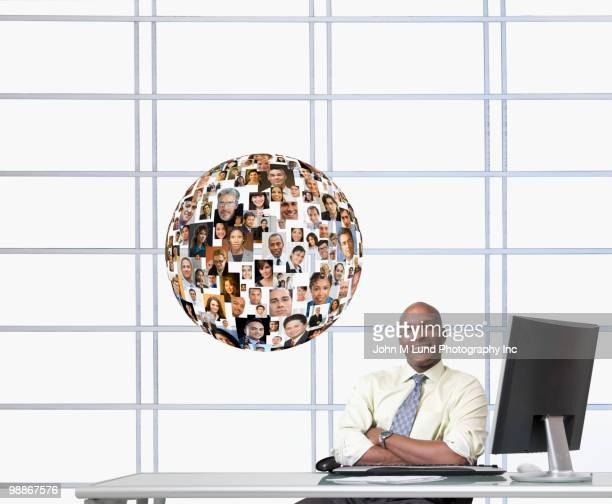 Black businessman at desk with floating globe of faces