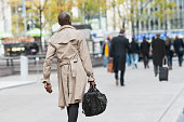 Black businessman carrying bag on city street