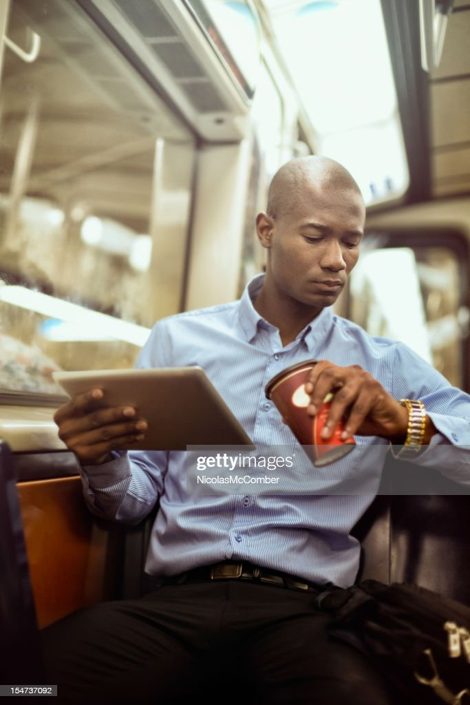 Black businessman checking time in subway : Stock Photo