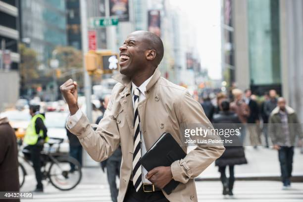 Black businessman cheering on city street
