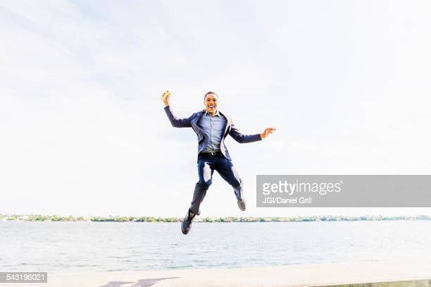 Black businessman jumping for joy at waterfront