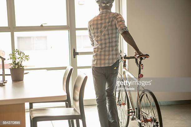 Black businessman leaving office with bicycle