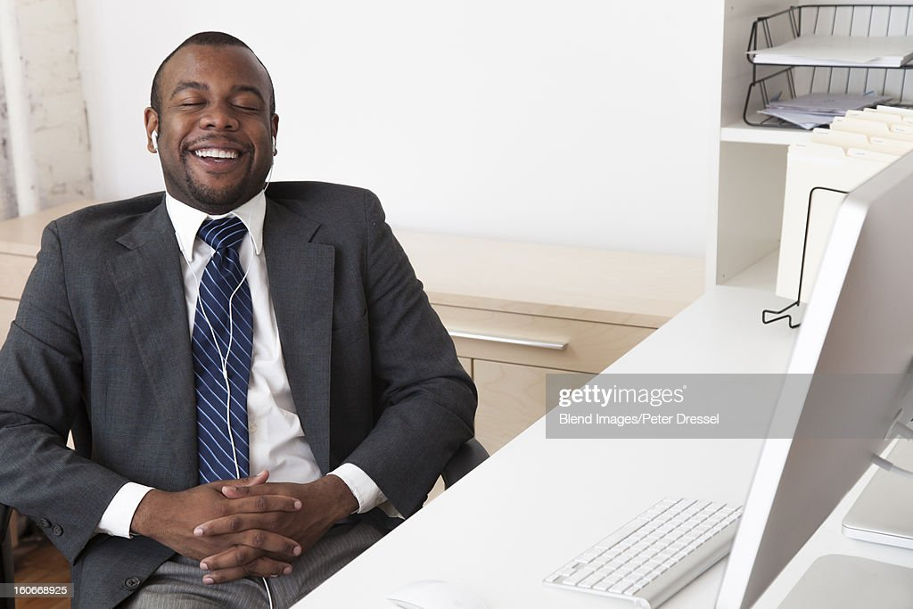 Black businessman listening to music at desk in office : Stock Photo