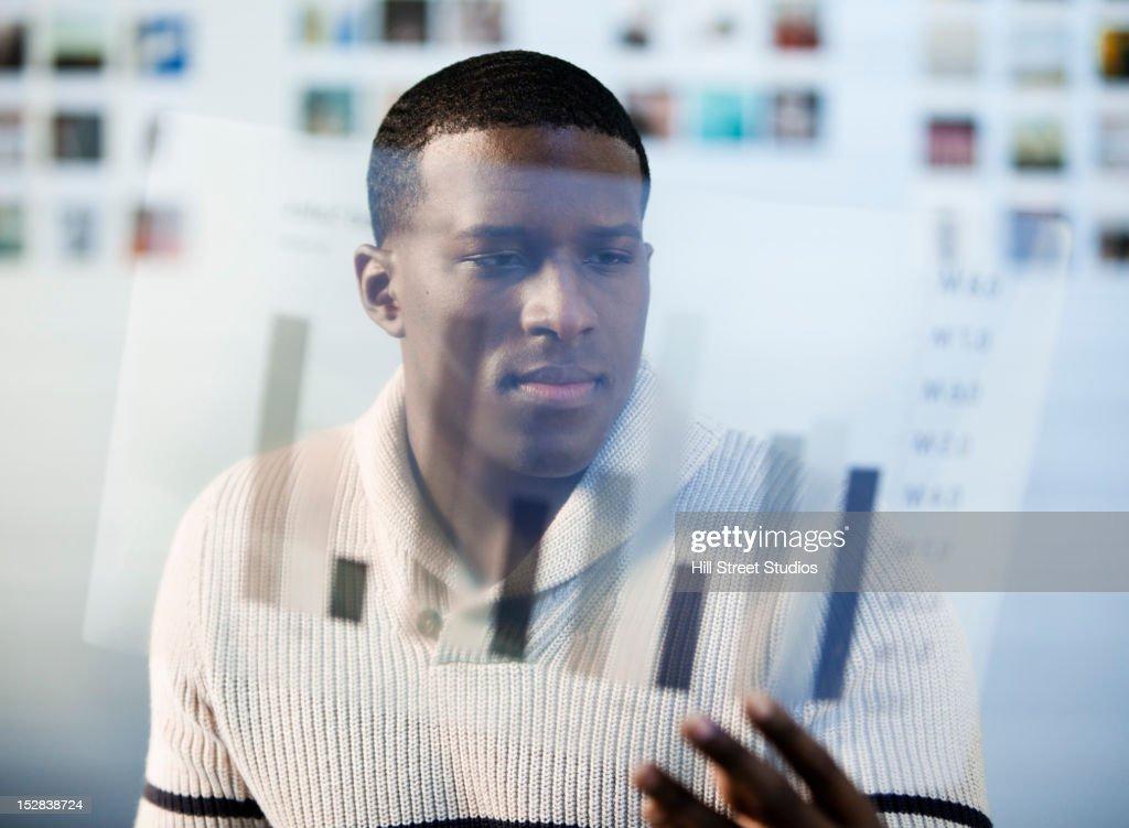 Black businessman looking at bar graph