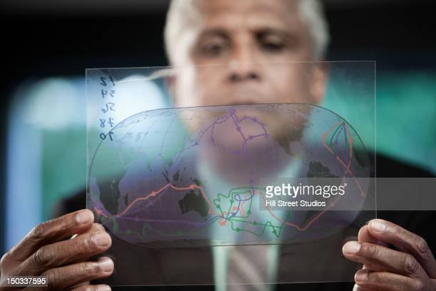 Black businessman looking at globe drawing
