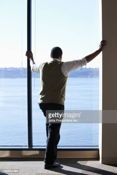 Black businessman looking out office window