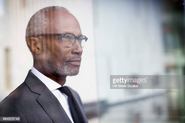 Black businessman looking out window