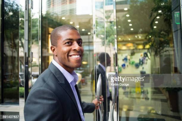 Black businessman opening office doors