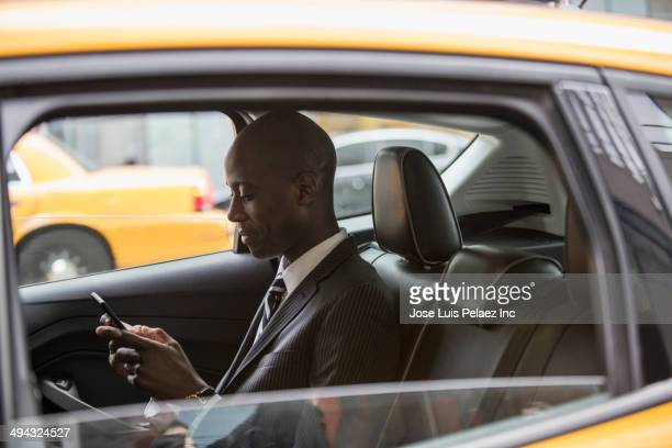 Black businessman riding in taxi on city street