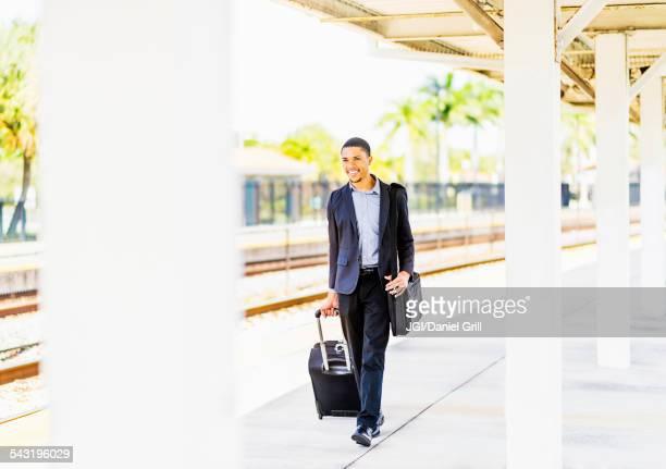 Black businessman rolling luggage on train platform