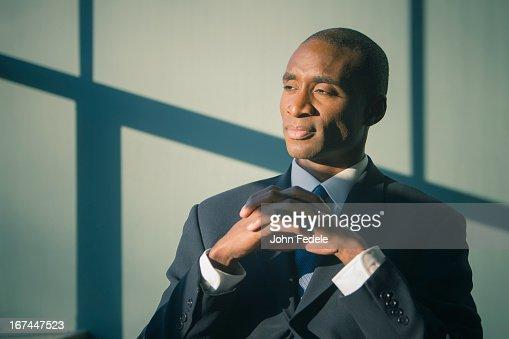 Black businessman sitting at desk : Stock Photo