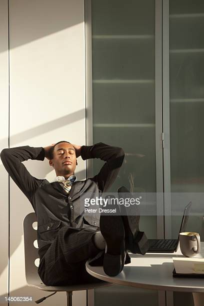 Black businessman sitting at desk with feet up