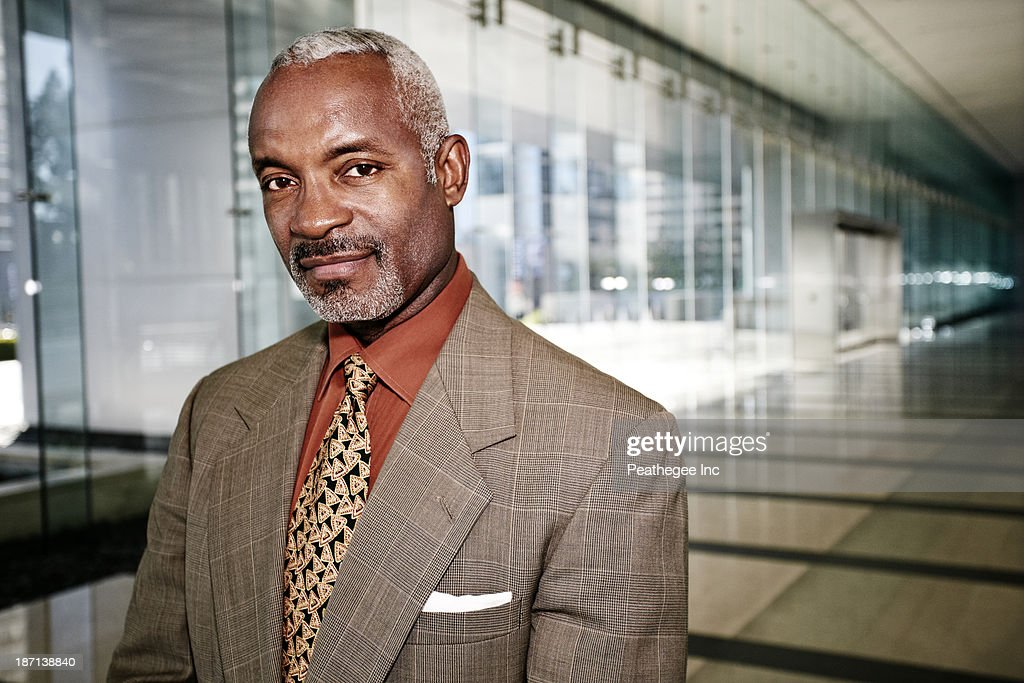 Black businessman smiling in office corridor : Stock Photo