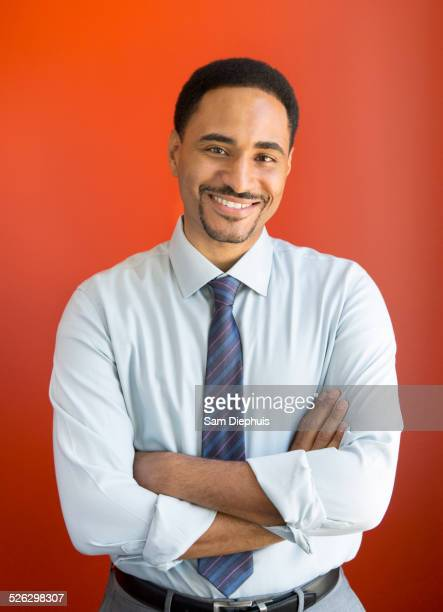Black businessman smiling with arms crossed