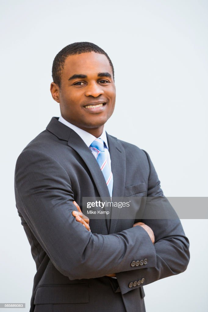 Black businessman smiling with arms crossed : Foto stock