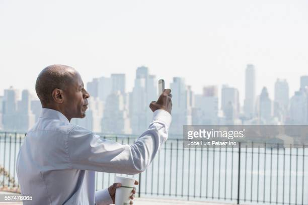 Black businessman taking cell phone photograph at city waterfront