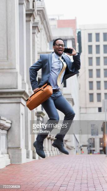 Black businessman talking on cell phone jumping for joy