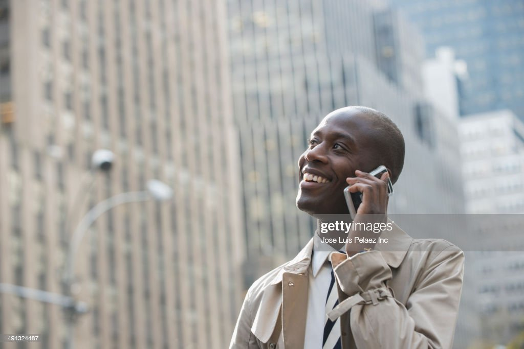 Black businessman talking on cell phone on city street : Stock Photo