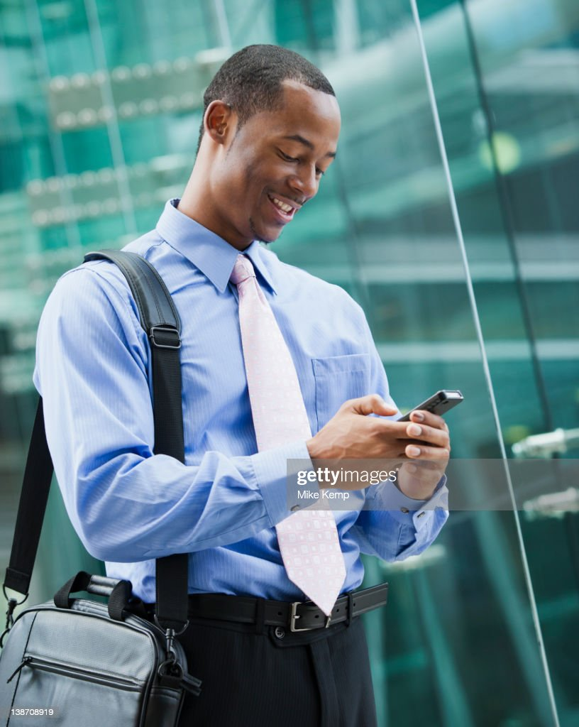 Black businessman text messaging on cell phone : Stock Photo