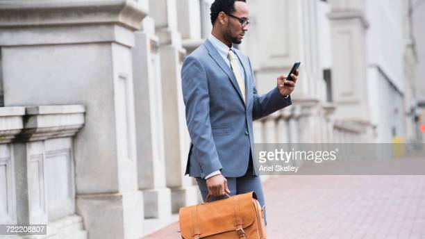 Black businessman texting on cell phone