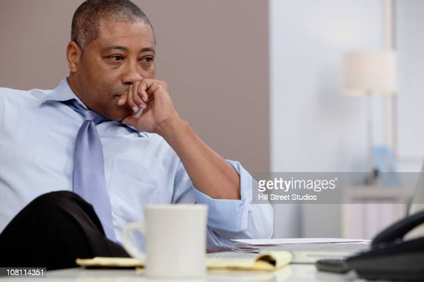 Black businessman thinking at desk in office