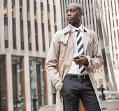 Black businessman using cell phone in city