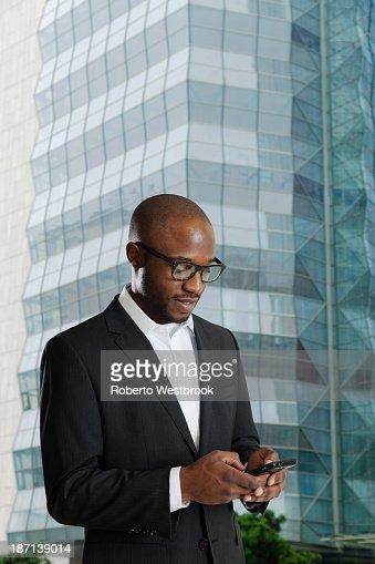 Black businessman using cell phone on city street : Stock Photo
