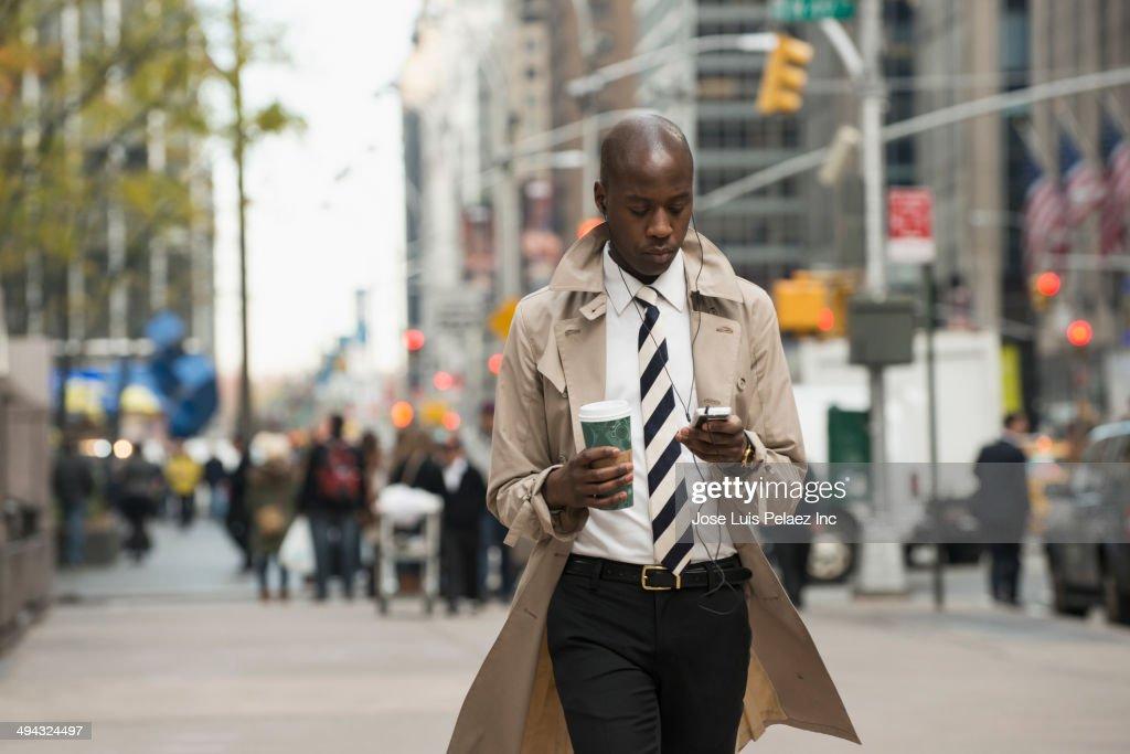 Black businessman using cell phone on city street : Stock-Foto