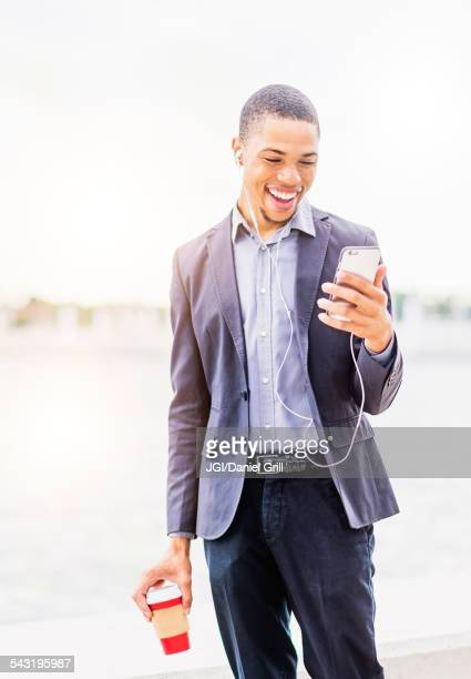 Black businessman using cell phone outdoors