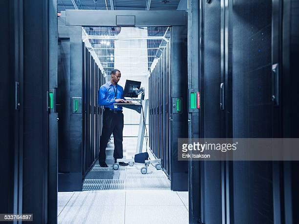 Black businessman using computer in server room