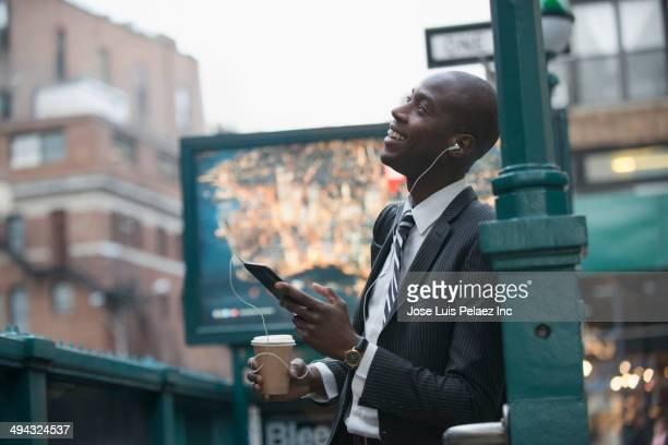 Black businessman using digital tablet by subway entrance