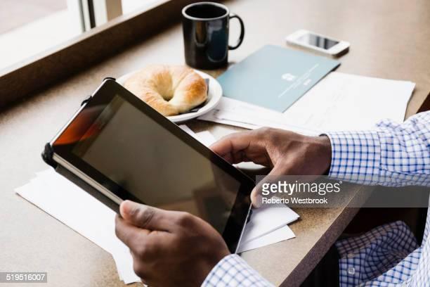 Black businessman using digital tablet in cafe