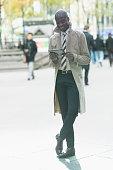 Black businessman using digital tablet on city sidewalk