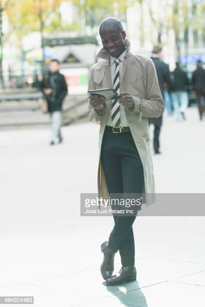 Black businessman using digital tablet on city sidewalk